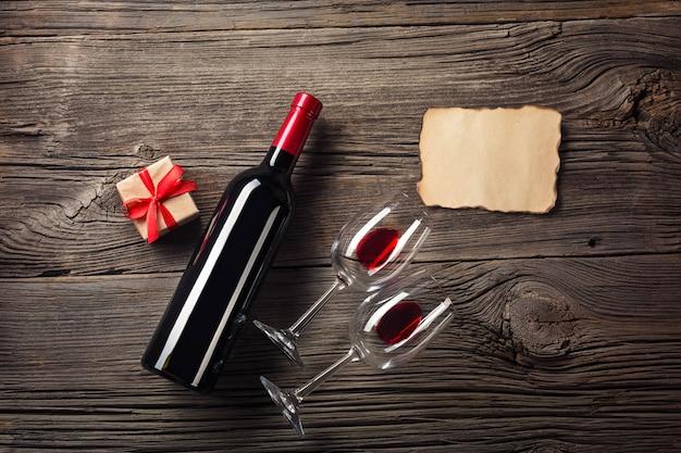 Walentynki kartkę z życzeniami. czerwone wino, pudełko i okulary na drewnianym stole. zobacz z miejscem na pozdrowienia.