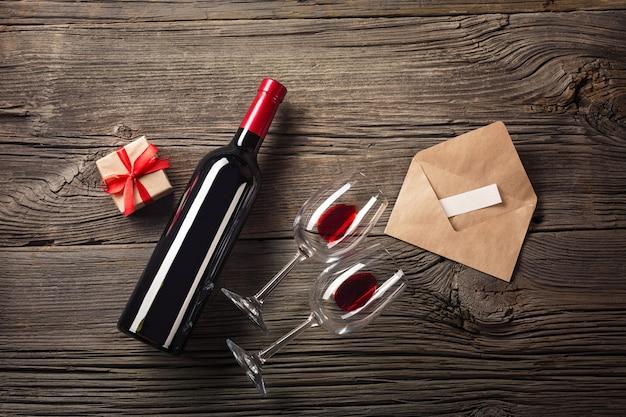 Walentynki kartkę z życzeniami. czerwone wino, pudełko i okulary na drewnianym stole