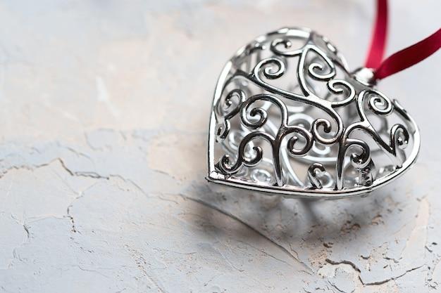 Walentynki kartkę z życzeniami, piękne srebrne serce z czerwoną wstążką na szarym tle z teksturą