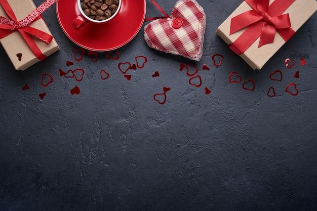 Walentynki kartkę z życzeniami. pudełko z czerwoną wstążką i kubkiem z ziarenkami aromatycznej kawy, figurki serca