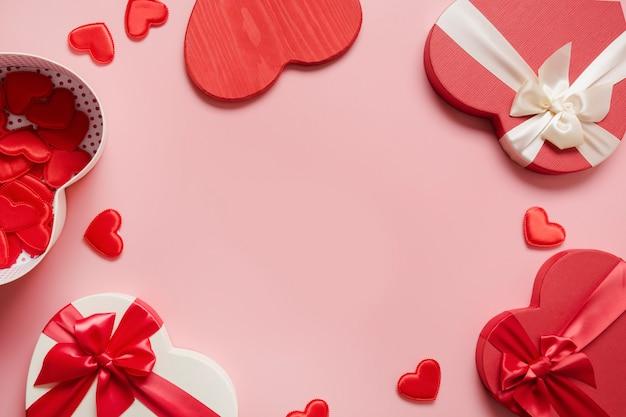 Walentynki kartkę z życzeniami. rama czerwonych pudełek w kształcie serca i wiele małych serc na różowo. widok z góry.
