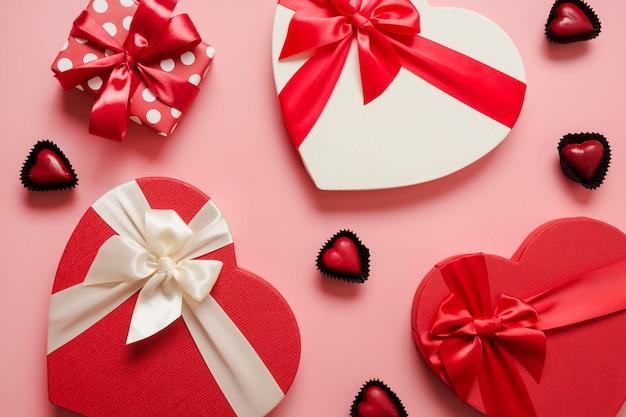 Walentynki kartkę z życzeniami. wzór czerwonych pudeł na prezenty w kształcie serca i czekoladowe słodycze na różowo. widok z góry.