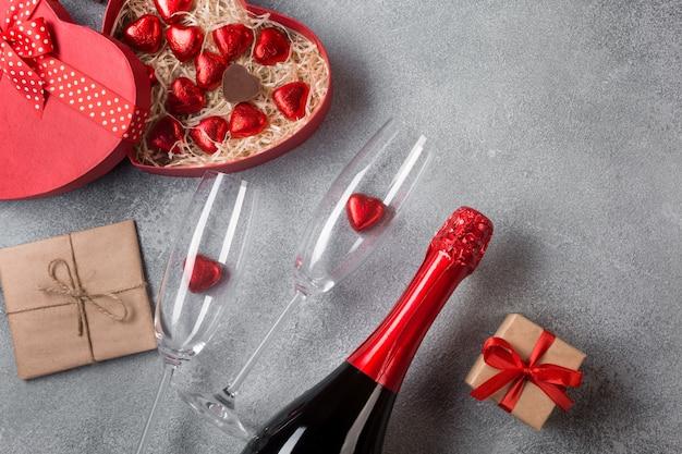 Walentynki kartkę z życzeniami z kieliszkami do szampana i cukierków serca na tle kamienia.
