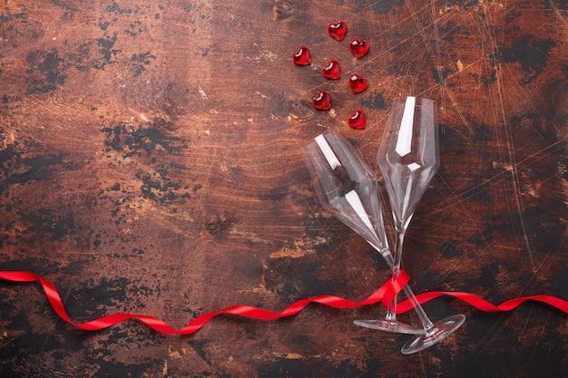 Walentynki kartkę z życzeniami z kieliszki do szampana, ozdobne serca i czerwoną wstążką na drewnianym tle kopiowanie miejsca widok z góry