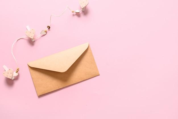 Walentynki kartkę z życzeniami z kopertą i sercami na różowym tle. widok z góry. skopiuj miejsce.