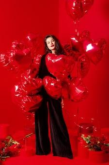 Walentynki kobieta w czerni z czerwonymi balonami w kształcie serca, bawiąca się