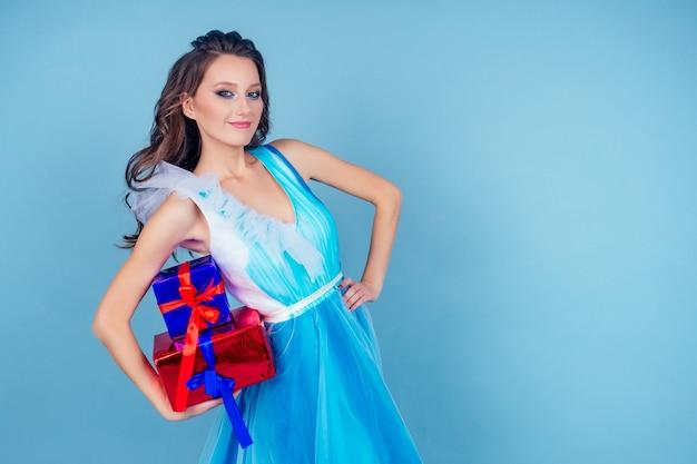 Walentynki kobieta w sukience trzymająca pudełko z prezentami na niebieskim tle w studio.miła dziewczyna otrzymała prezent zaskoczona i zdumiona.koncepcja międzynarodowego dnia kobiet i dnia matki