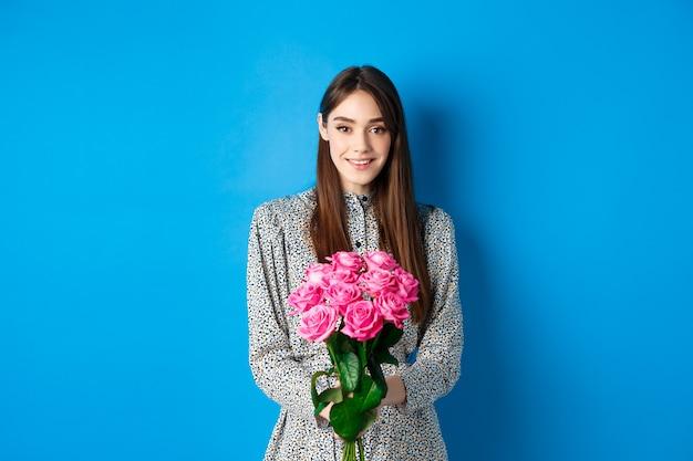 Walentynki koncepcja delikatna młoda kobieta w sukience trzymająca bukiet róż na romantycznej randce stojąca...