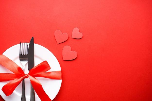 Walentynki. koncepcja miłości. dzień matki. serca ze sztućcami na białym talerzu z czerwoną wstążką na czerwonym tle, leżał płasko, z miejscem na tekst.