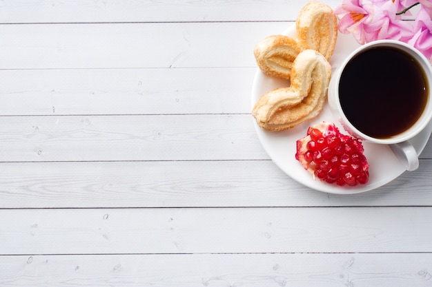 Walentynki koncepcja śniadanie. filiżanka kawy i ciastka serca na białym stole. kopia przestrzeń, leżał płasko.