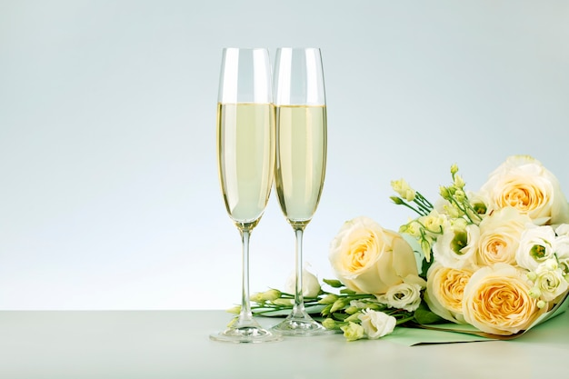 Walentynki, koncepcje rocznicowe. dwie szklanki szampana i bukiet róż z miejscem na tekst.