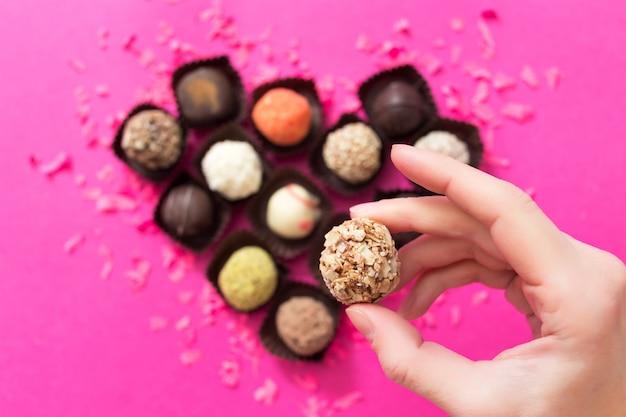 Walentynki. kształt serca wykonany z cukierków czekoladowych na różowym tle. ręka kobiety bierze cukierki