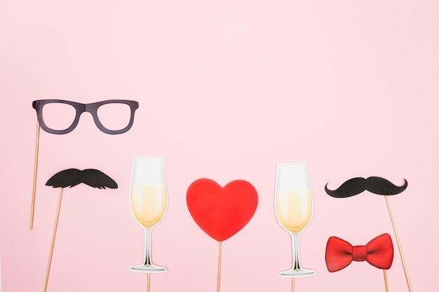 Walentynki lgbt koncepcja czerwone serce, kieliszki do szampana z parą papierowych wąsów rekwizyty na różowym tle