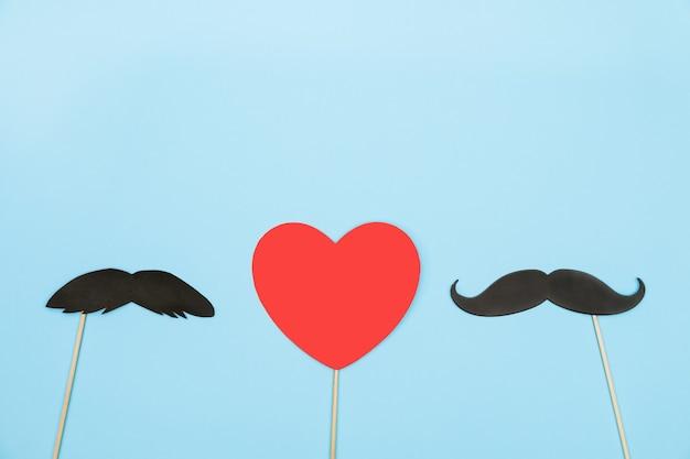 Walentynki lgbt koncepcja czerwone serce z kilkoma papierowymi wąsami rekwizyty na niebieskim tle