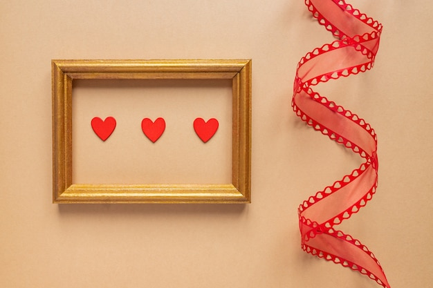 Walentynki lub koncepcja romantyczny ślub. skręcona ozdobna wstążka i złota ramka na zdjęcia z czerwonymi sercami na beżowym tle.