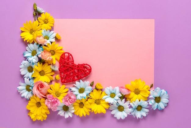 Walentynki lub ślub romantyczny koncepcja z kwiatami i czerwonym sercem na różowym tle. widok z góry, miejsce na kopię.