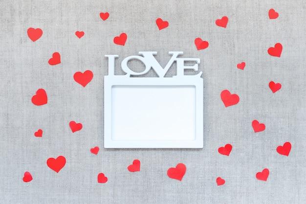 Walentynki makieta z białą ramą z słowo miłość i wiele czerwonych serc