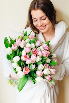 Walentynki - marzenie zmysłowej młodej kobiety z bukietem kwiatów. słoneczny wiosenny poranek.
