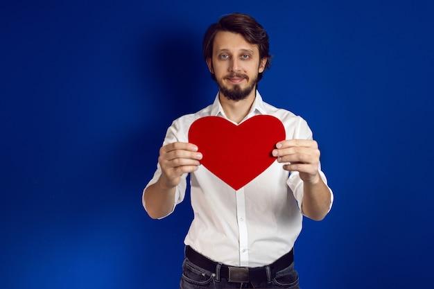 Walentynki, mężczyzna z brodą w białej koszuli na niebieskiej ścianie trzyma czerwone serce