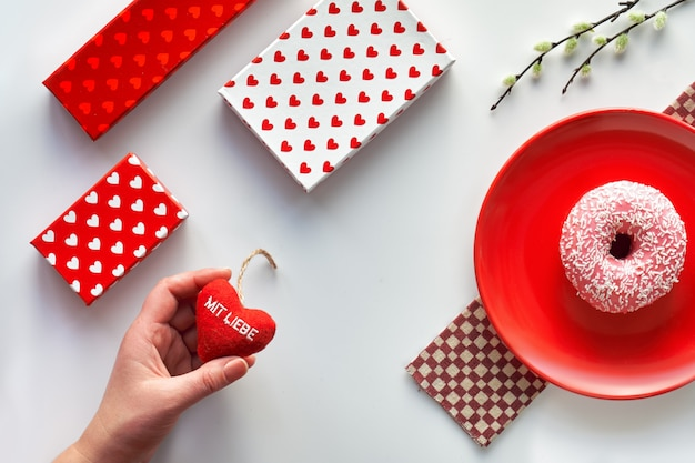"""Walentynki mieszkanie leżał, widok z góry na białym tle. geometryczny z wierzbą cipki. pudełka do prezentów, różowy pączek na czerwonym talerzu i serce w dłoni. niemiecki tekst """"mit liebe"""" na sercu oznacza """"z miłością""""."""