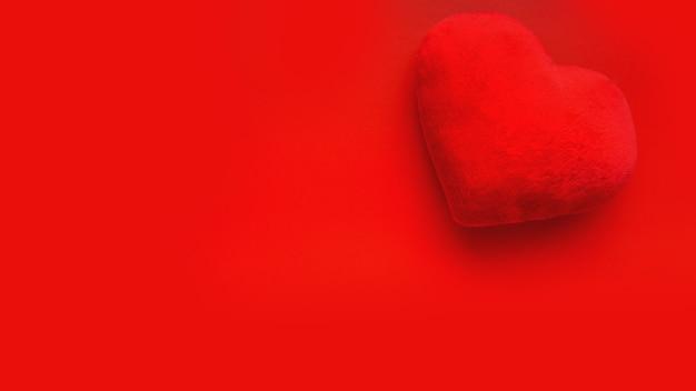 Walentynki miłość powierzchni z miękkim sercem na czerwonej powierzchni. widok z góry. projekt banera, karty