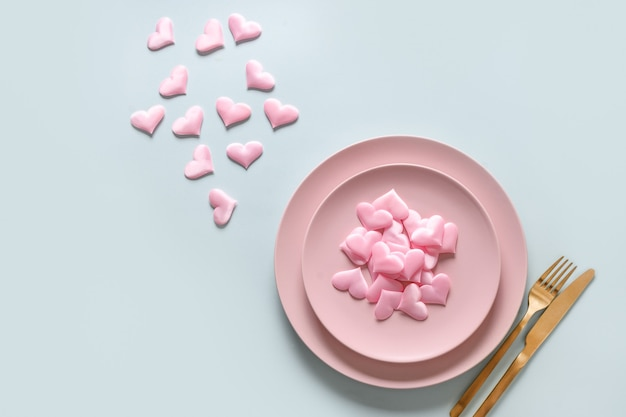 Walentynki nakrycie stołu z różowymi romantycznymi sercami i złotymi sztućcami na niebieskim tle. zaproszenie z miejscem na kopię.