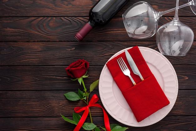 Walentynki nakrycie stołu z talerzem, winem i kieliszkami