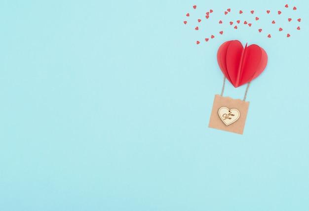 Walentynki niebieski z czerwonym balonem w kształcie serca z koszem z drewnianym sercem i mnóstwem czerwonych serc