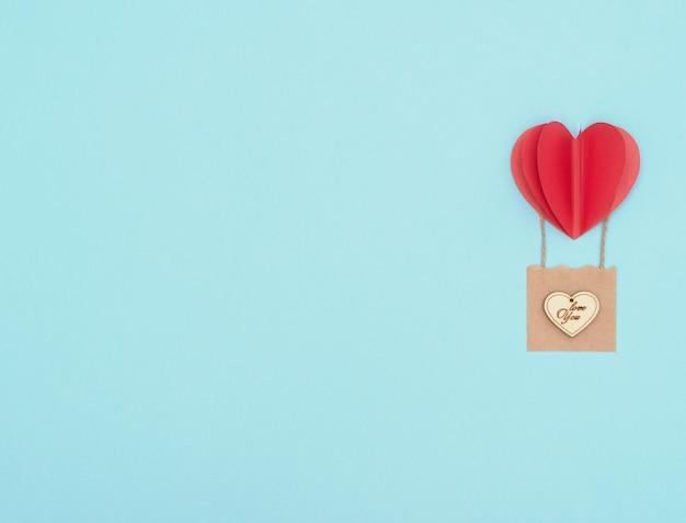 Walentynki niebieskie tło z czerwonym balonem serca z koszem rzemieślniczym z drewnianym sercem na nim.