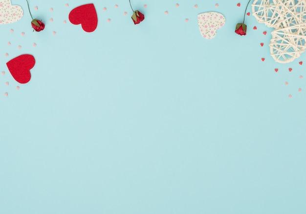Walentynki niebieskie tło z rattanem i filcowymi sercami, czerwonymi różami i małymi czerwonymi i różowymi serduszkami. powitanie, karta z zaproszeniem.