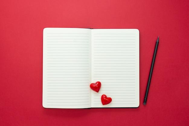 Walentynki. otwiera notatnika z czerwonymi sercami i ołówkiem na czerwonym tle, kopii przestrzeń dla teksta.