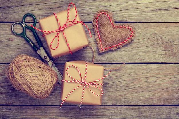 Walentynki pakowanie prezentów z pudełka i nożyczki na białym drewnianym stole. stonowane