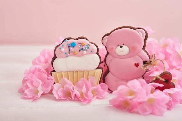 Walentynki. piernikowi niedźwiadkowi ciastka z kwiatami na różowym tle.