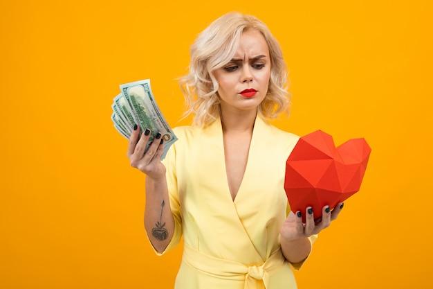 Walentynki . portret seksownej blond dziewczyny z czerwonymi ustami z czerwonym sercem z papieru i pieniędzy w ręce na żółtym