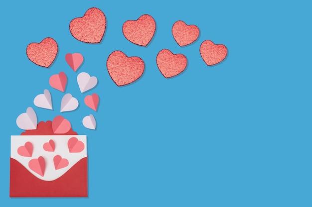 Walentynki pozdrowienia koncepcja z koperty i czerwone serca na niebieskim tle widok z góry z miejsca kopiowania tekstu