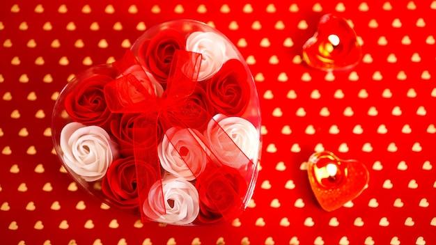 Walentynki prezent na czerwonym tle. dużo czerwonych i białych róż w opakowaniu w kształcie serca, przewiązanych czerwoną wstążką. pojęcie miłości