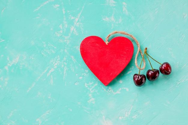 Walentynki, prezent niespodzianka z czerwoną wiśnią. zdrowa żywność. czerwone wiśnie jagodowe, drewniane serce. lato miłość, martwa natura na pastelowym tle. leżał płasko, widok z góry. skopiuj miejsce miłość do wiśni. romantyczny