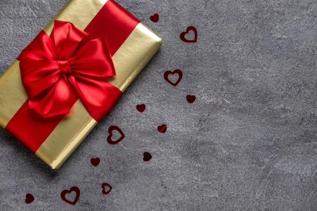Walentynki prezent z czerwoną wstążką na szarym tle betonu. koncepcja walentynki. kopia miejsca. widok z góry.