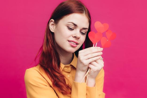 Walentynki prezenty kobieta z sercem na kij na różowym tle copy space. wysokiej jakości zdjęcie