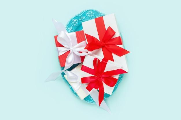 Walentynki, prezenty na owalnym naczyniu na pastelowym niebieskim tle. koncepcja walentynki.