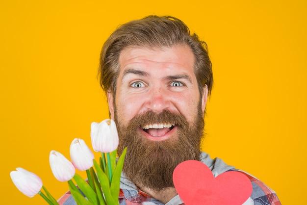Walentynki przedstawia brodaty mężczyzna z sercem i kwiatami walentynki reklama walentynkowa