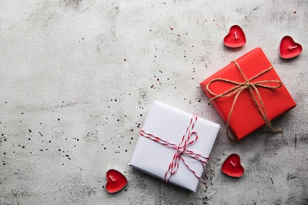 Walentynki, pudełko papieru kraft ze wstążką i świecami na szarym tle.
