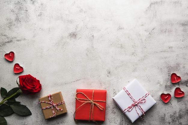 Walentynki, pudełko papieru kraft ze wstążką, różą i świecami na szarym tle
