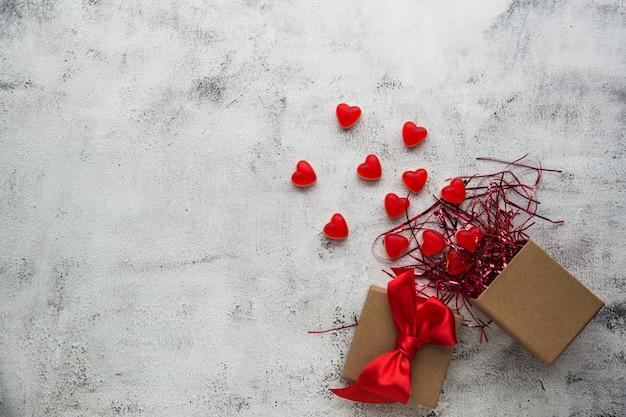 Walentynki, pudełko z papieru pakowego z cukierkami w kształcie czerwonego serca. szare tło.
