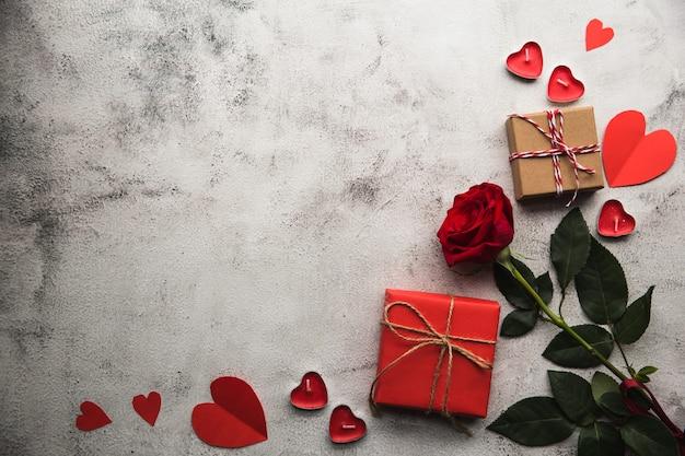 Walentynki, pudełko z papieru pakowego ze wstążką, papierowym sercem i świecami.