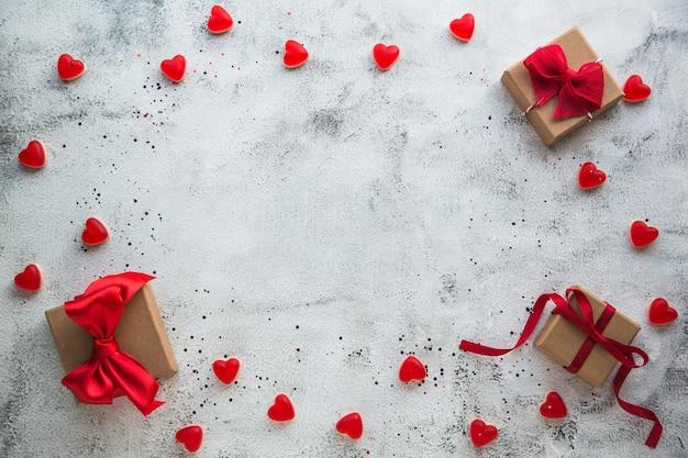 Walentynki, pudełko ze wstążką i cukierkami w kształcie serca na szarym tle.