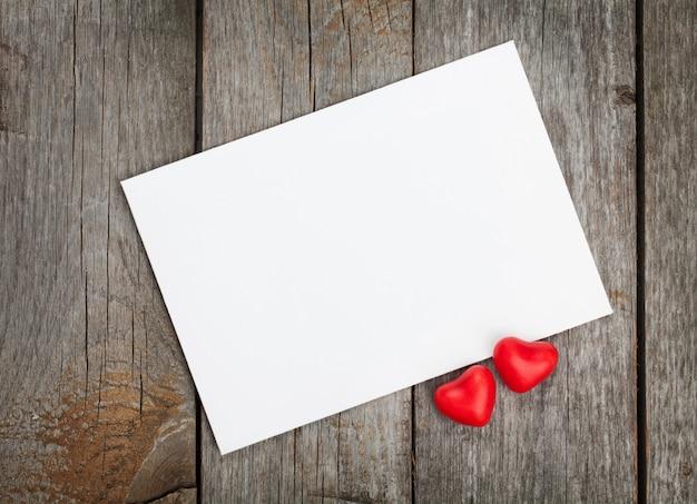 Walentynki pusta karta podarunkowa i czerwone cukierkowe serca na drewnianym tle