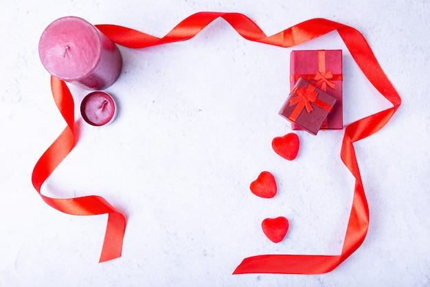 Walentynki. rama wykonana z serca, świece, prezenty i wstążki na białym tle.