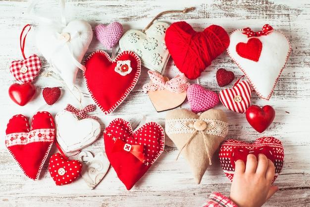 Walentynki ręcznie robione serca na odrapanym drewnianym stole i dłoni dziecka