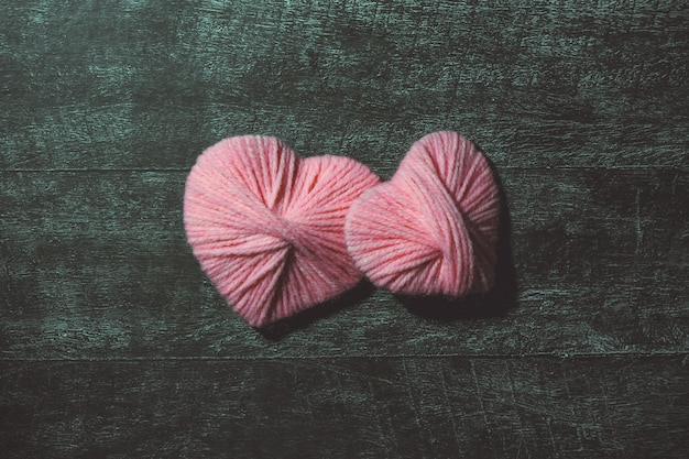 Walentynki. ręcznie wykonane ozdobne nici różowe serca na ciemnym drewnianym stole. koncepcja miłości. kartka z życzeniami. copyspace